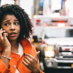 Image of a woman on the phone in front of an approaching ambulance with an incredulous look on her face implying she's shocked to find out workers' compensation issues shut down her Pittsburgh borough's emergency service provider.